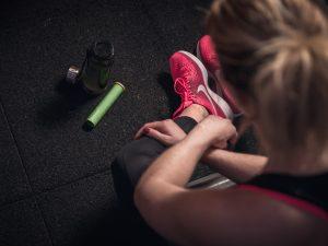 Kvinna bakifrån sittande på golvet med träningskläder, stomacol rehydrate grönt rör ligger bredvid