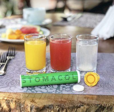 Stomacol rehydrate grönt rör med vätskeersättning bredvid glas med juice