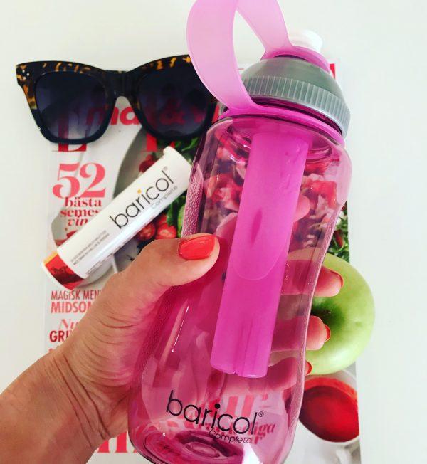 hand håller rosa Baricol vattenflaska, med tidning, solglasögon, äpple och ett rör Baricol complete brustabletter i bakgrunden