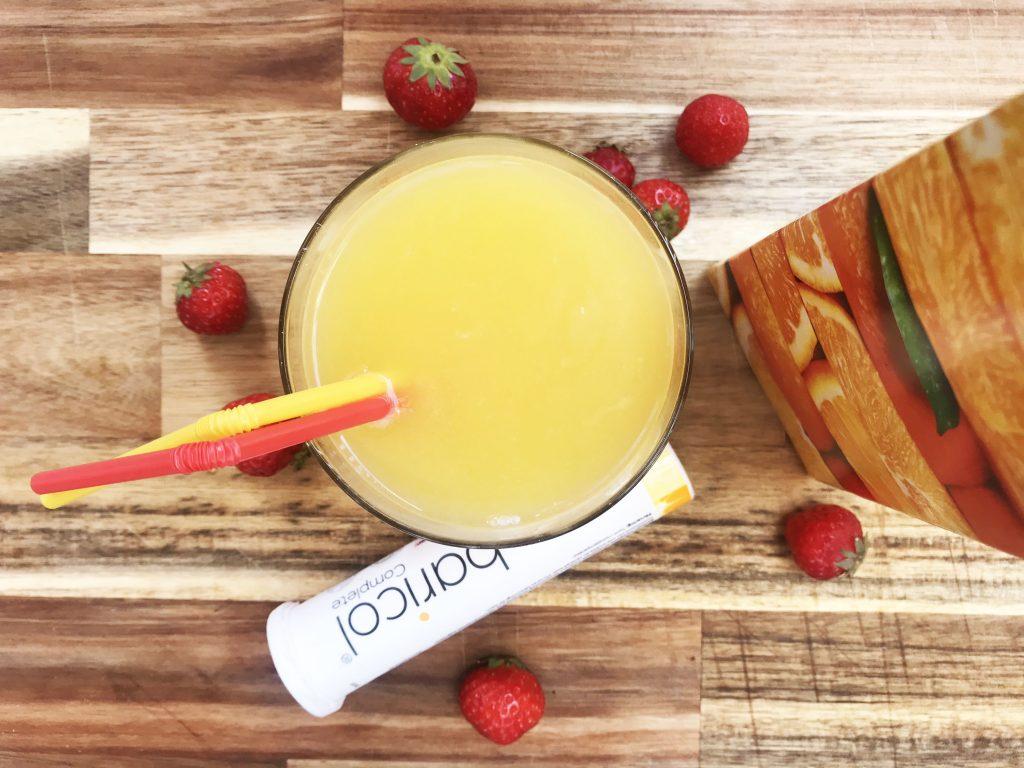 Baricol Complete brustablett blandat med apelsinjuice i ett glas med två sugrör, ett Baricol rör, på träunderlag, juicepaket omgiven av jordgubbar