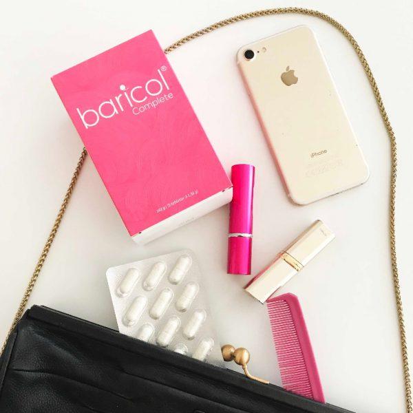 bild mot vitt bord med svart väska, baricol complete förpackning, iPhone, läppstift, parfym och blisterkarta med vitaminer