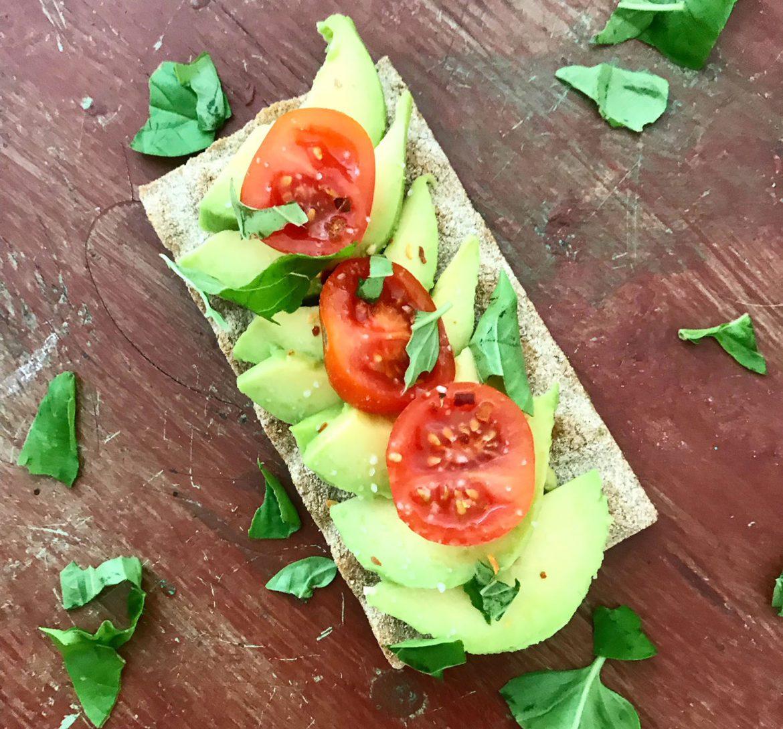 avokado på knäckebröd med tomat och basilika