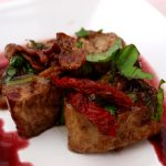 2 skivor kött på tallrik med soltorkade tomater rödvinssky och basilika