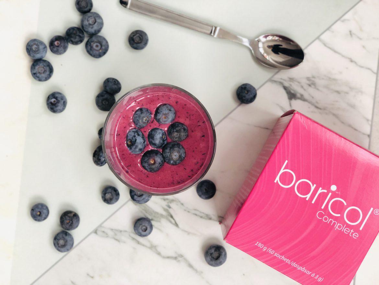 Baricol Complete pulver rosa ask, bredvid glas med blåbärssmoothie omgiven av blåbär
