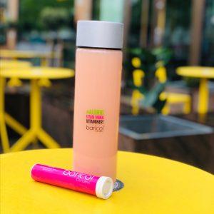 Baricol Complete brusrör i rosa på gult bord med vattenflaska