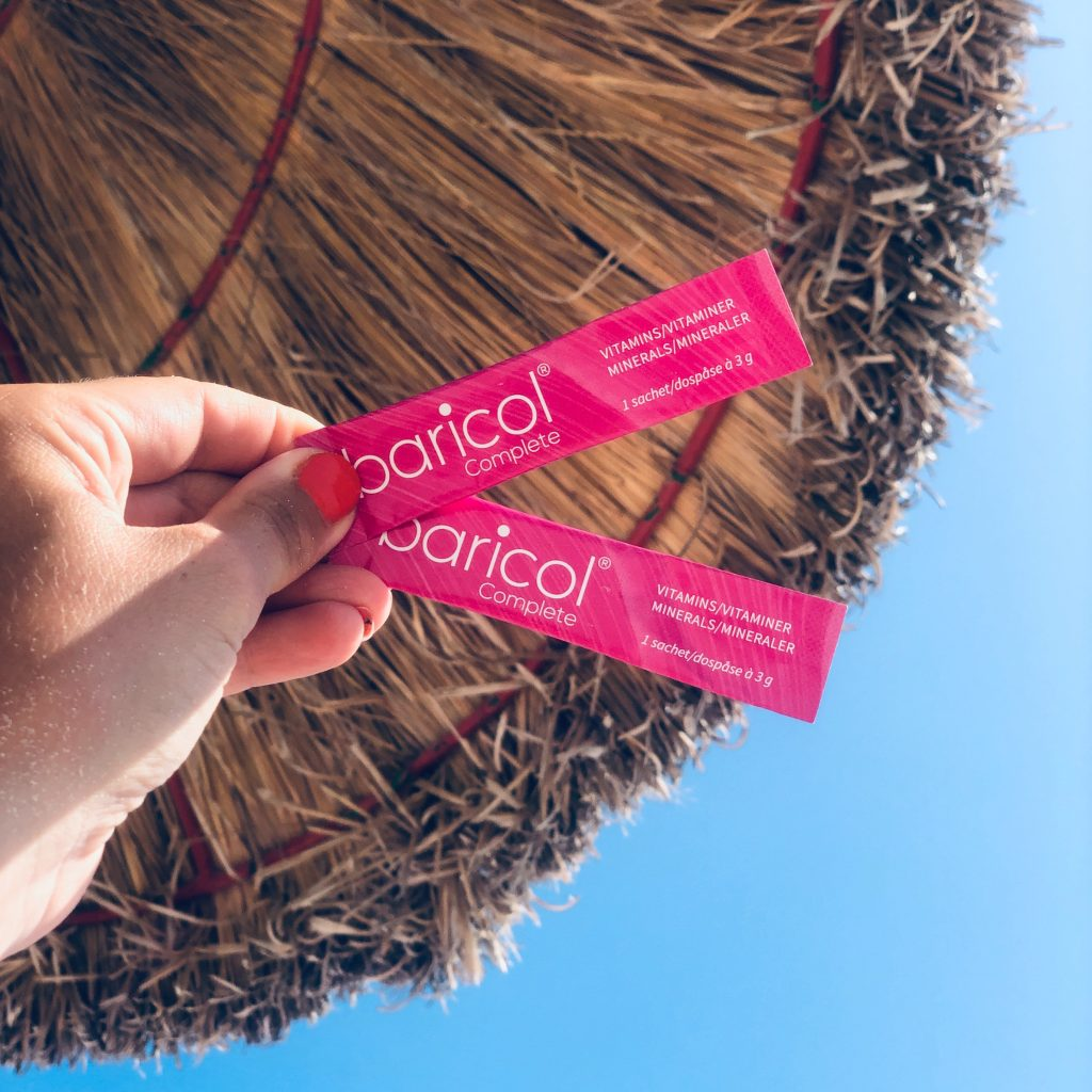 Två rosa Baricol complete pulversticks hålls mot blå himmel och stråparasoll