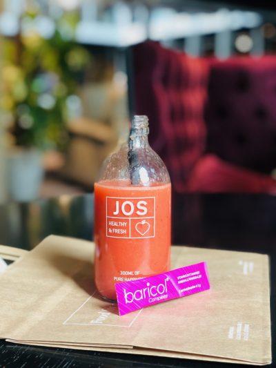 Glasflaska från JOS med röd juice och ett rosa pulverstick baricol framför