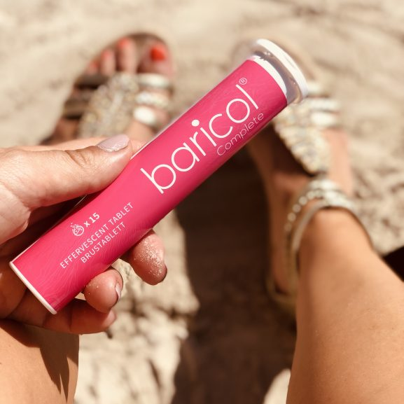 Baricol complete brusrör rosa hålls mot fötter på sandstrand