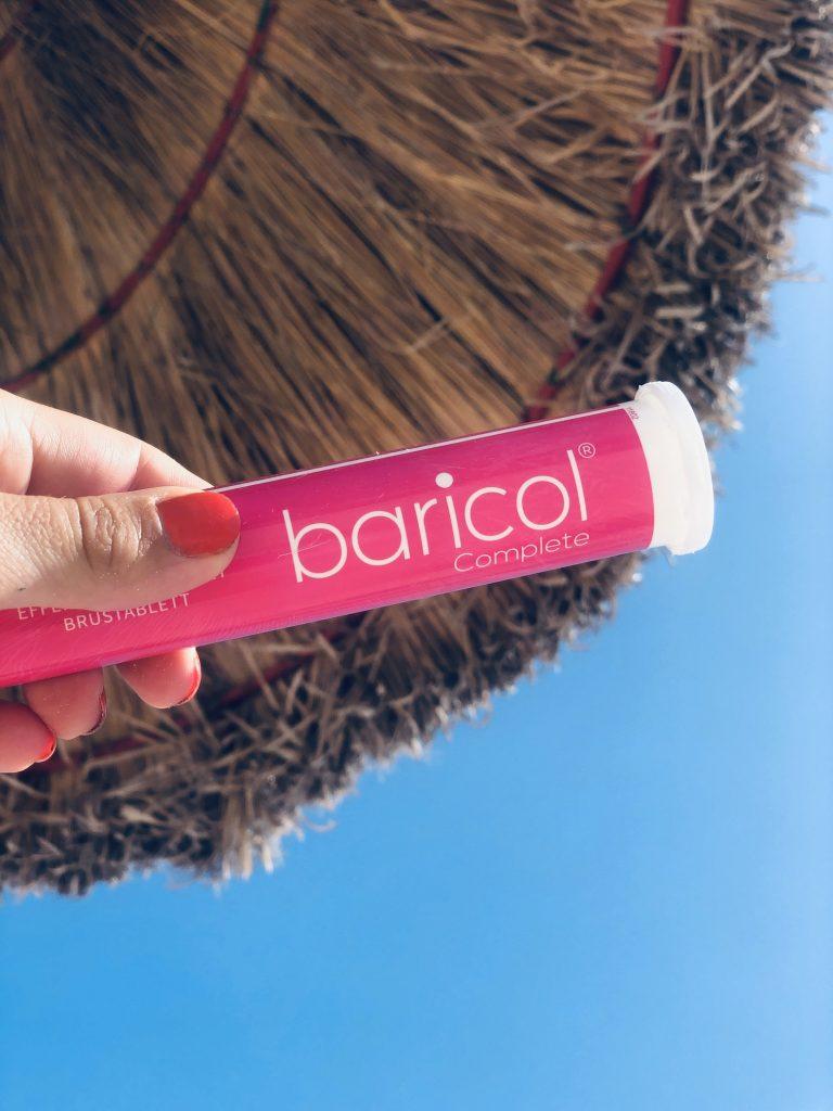 Baricol complete brusrör rosa hålls mot stråparasoll och blå himmel