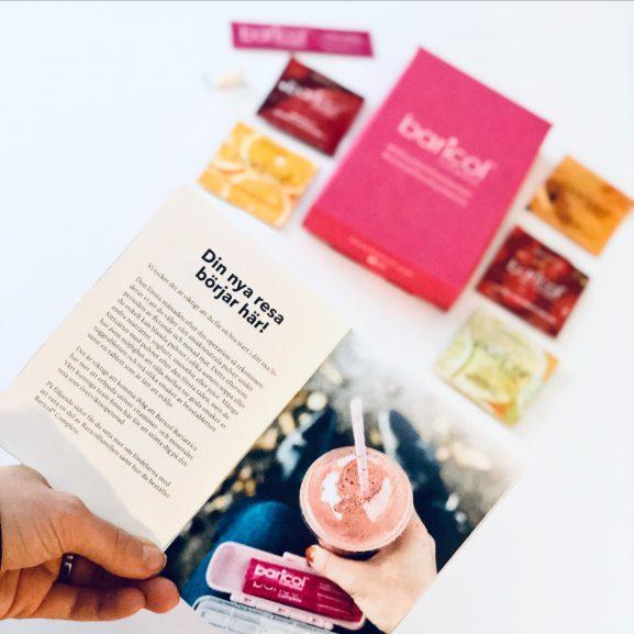 Rosa ask med baricol complete prover på vitaminer, broschur med texten din nya resa börjar här