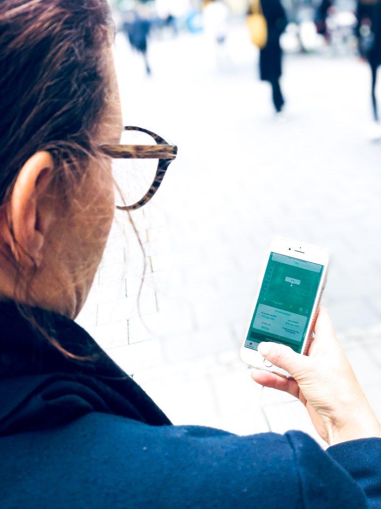 Glasögonprydd kvinna håller i telefon med appen BariBuddy på stan