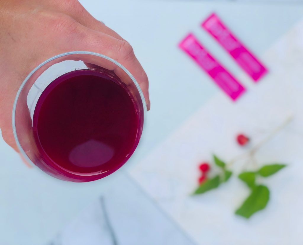 Hand håller i glas med hallonjuice, i suddig bakgrynd syns baricol rosa sticks