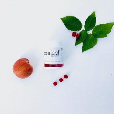 Baricol complete tuggtablett på vitt bord omgiven av hallon och persika