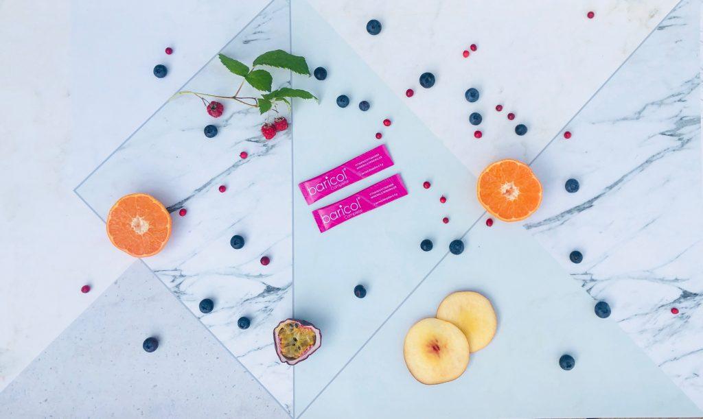 Bild över bord där det ligger två rosa sticks med baricol complete pulver omgiven av frukter och bär
