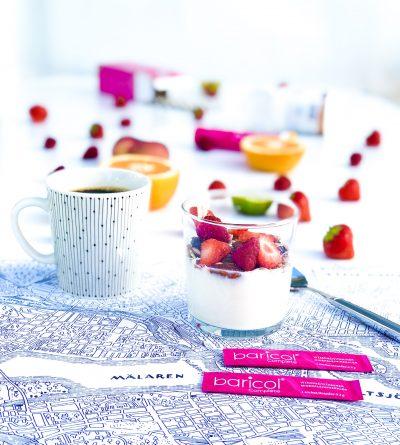 Frukostunderlägg med stockholmskarta på den står kaffekopp, glas med yoghurt med granola och jordgubbar omgiven av två dospåsar baricol pulver