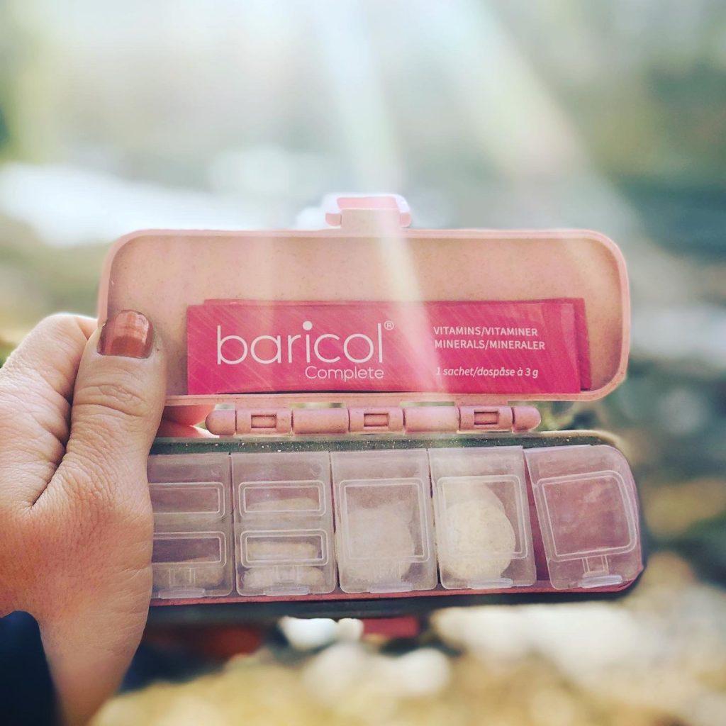 Rosa Baricol tablettetui för vitaminer hålls mot solen