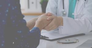 Läkare håller patientens hand
