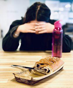 Dumping efter måltid, kvinna sitter med ansiktet i händerna efter att ha ätit en bulle