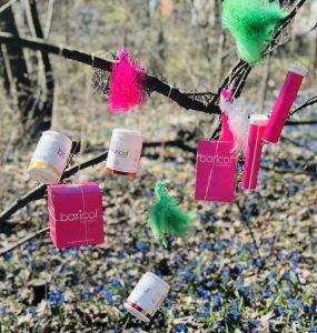 rosa Baricolförpackningar hänger i träder med fjädrar