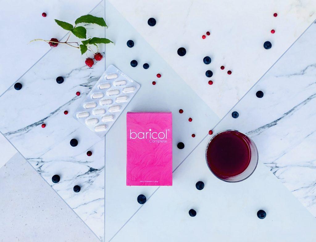 Baricol complete ask med vitaminer omgiven av hallonjuce och hallon och blåbär