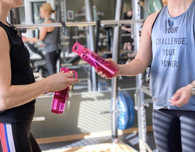 Två tjejer i gymmet skålar med rosa vattenflaska