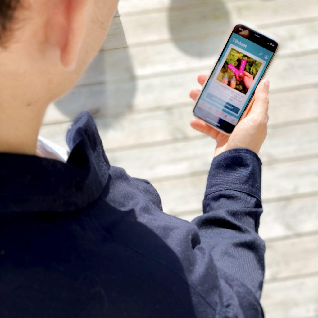 Man tittar i telefonen BAriBuddy app
