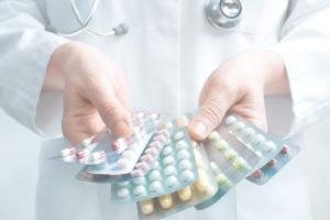 Hand håller i pillerkartor med läkemedel